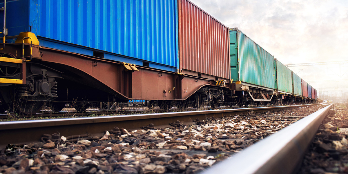 Train wagons carrying cargo containers for shipping companies