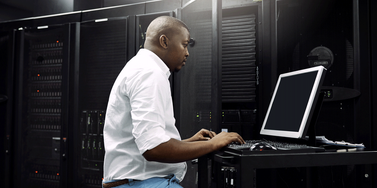 man at computer in server room